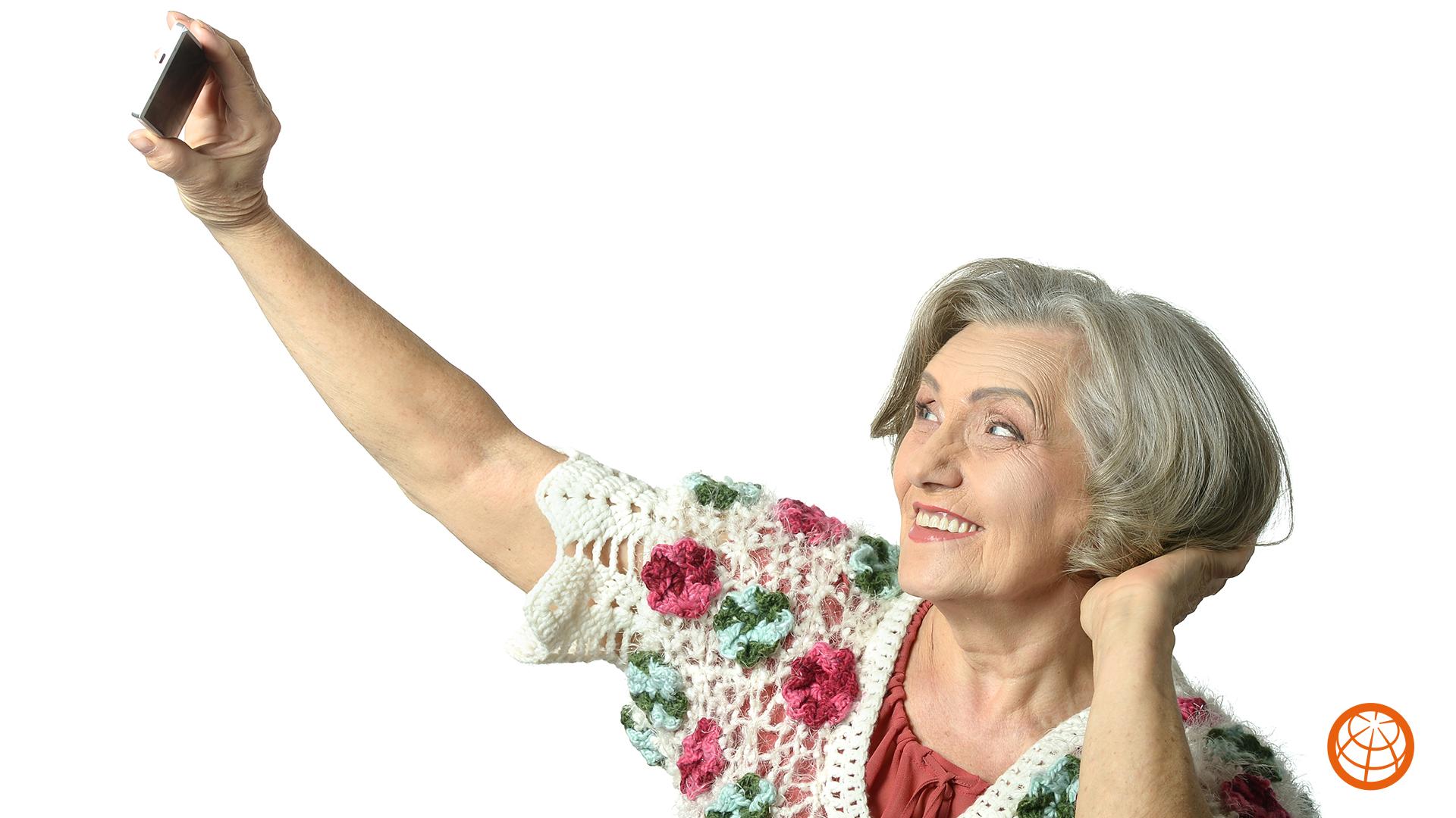 Ei gammel dame tar en selfie og smiler inn i mobilen