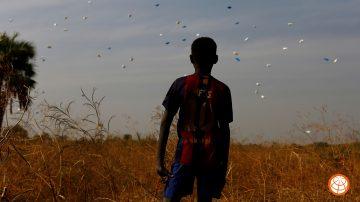 en gutt ser opp mot himmelen på sekker med mat som slippes fra et fly