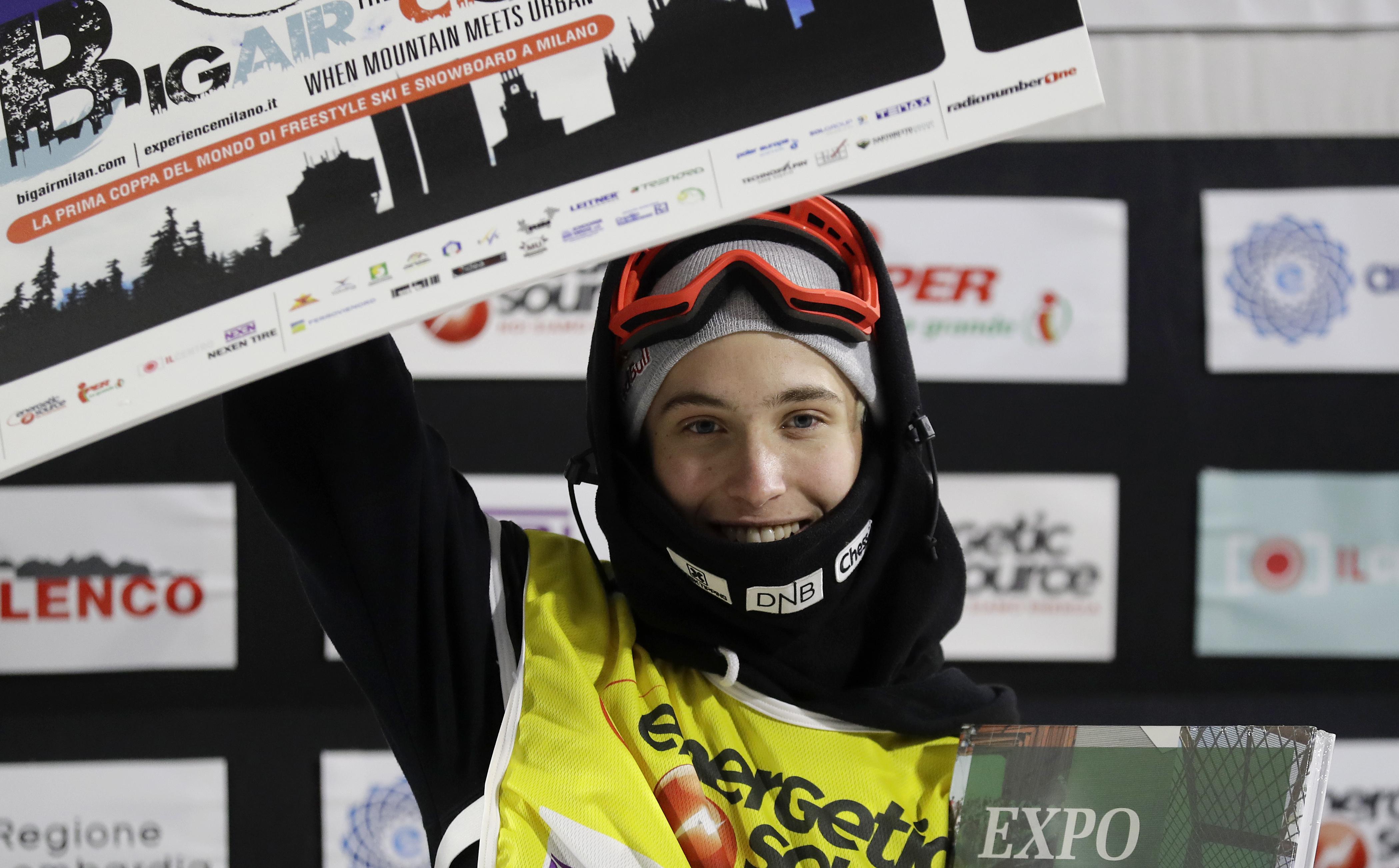 Snowboardkjører Marcus Kleveland holder brettet over hodet og feirer